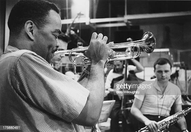 American swing and bop trumpeter Clark Terry with jazz saxophonist Stan Getz in the background right, circa 1960.
