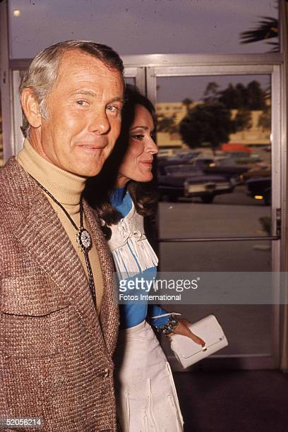 American talk show host and comedian Johnny Carson wears a turtleneck shirt and bolo tie as he walks with his third wife Joanna Holland May 1972
