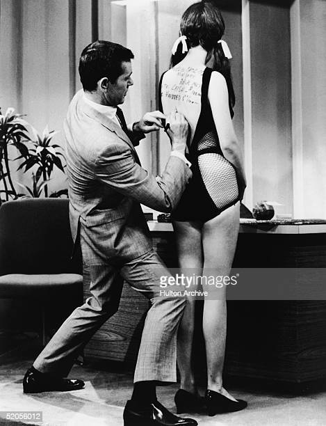 American talk show host and comedian Johnny Carson writes a check on the bare back of Judy Brown during a segment on his NBC late night talk show...