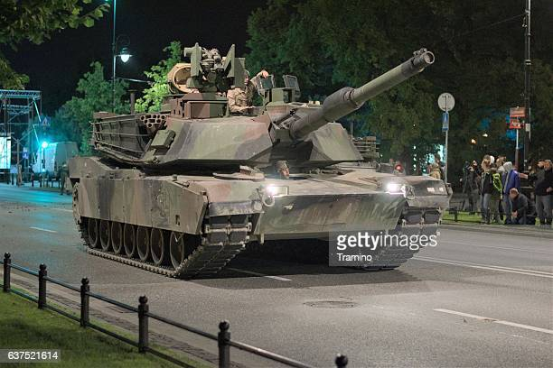american tank driving on the street at night - armored tank stock photos and pictures