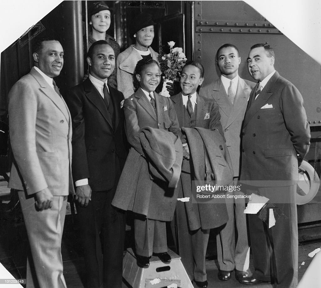 American tap dancers and entertainers the Nicholas Brothers, Harold (1921 - 2000) (fore, center left, standing on step) and Fayard (1914 - 2006) (fore, center right), pose next to a train, 1935. Among those with them is American newspaper publisher John H. Sengstacke (1912 - 1997) (second right).