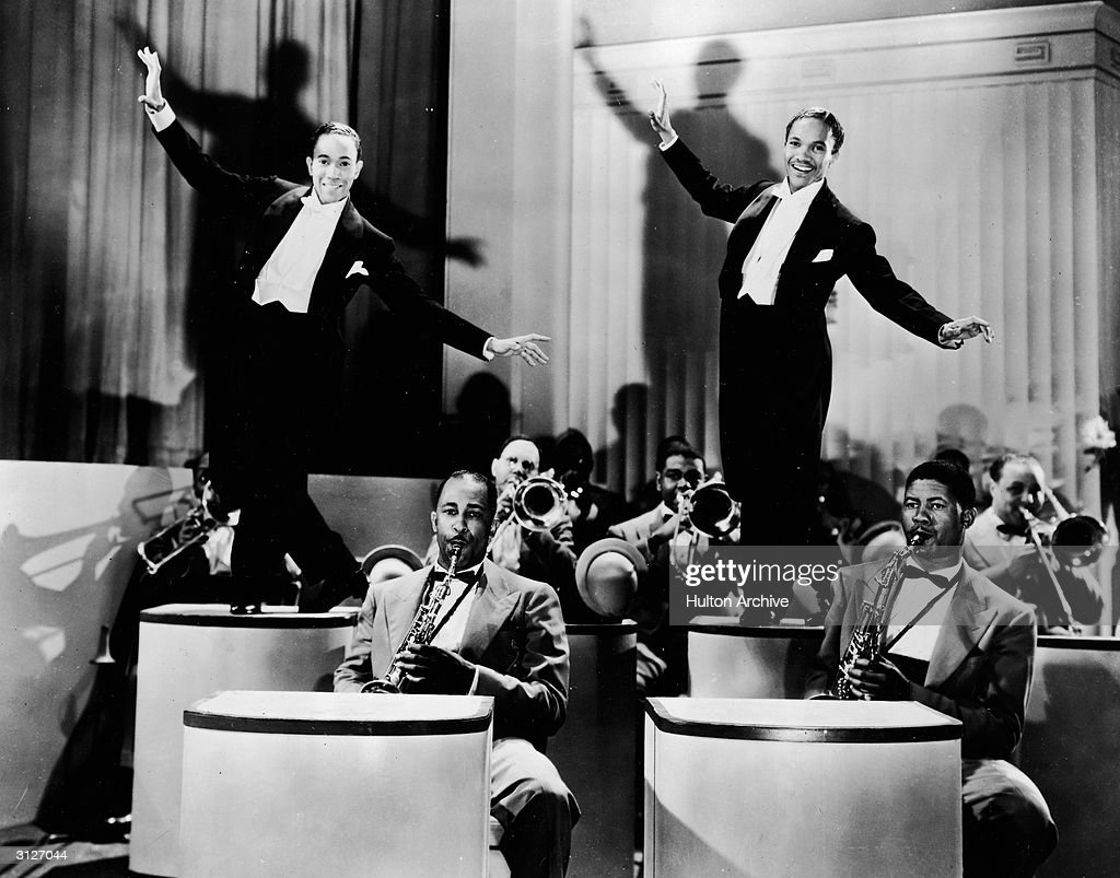 American tap dancing duo The Nicholas Brothers, featuring Harold (R) (1921 - 2000) and Fayard, perform on two pedestals, backed by an orchestra in an unidentified film still, 1940s.