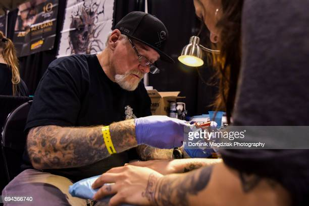 """American tattoo artist Brian Everett from Route 66 Fineline Tattoos tattoos a women during day one of the """"19th Annual Northern Ink Xposure Tattoo..."""