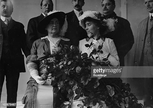American teacher Anne Sullivan Macy and her former student author and activist Helen Keller sit together while several dignitaries stand behind them...