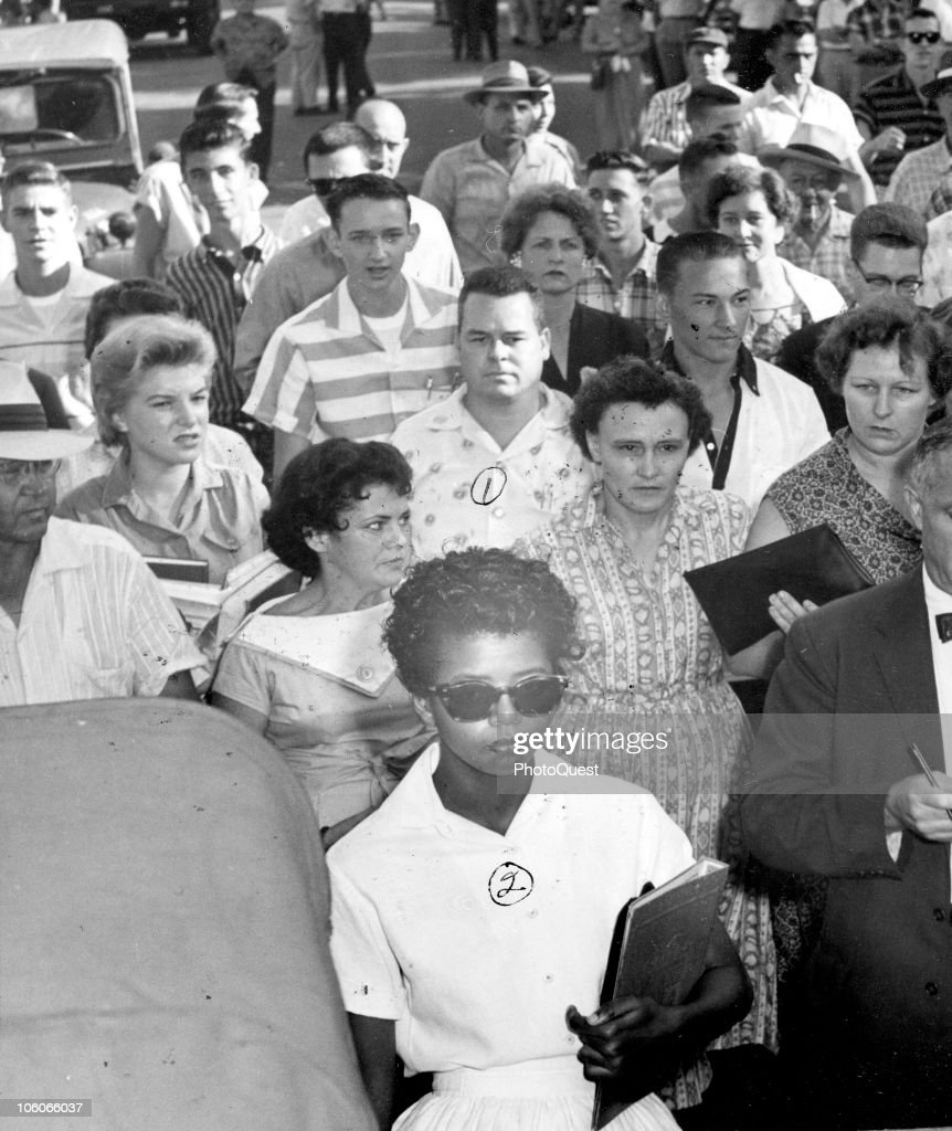 American teenager Elizabeth Eckford (center bottom, in suglasses) is followed by a crowd as she walks to school, Little Rock, Arkansas, September 23, 1957. Eckford and eight others, known as the Little Rock Nine had attempted to enroll in Little Rock Central High School and were initially prevented by Governor Orval Faubus who called on the National Guard to stop the school's integration.