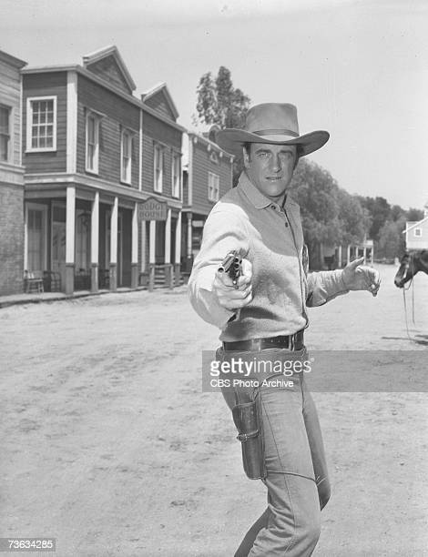American television actor James Arness born James Aurness draws a revolver from his holster in character as Marshall Matt Dillon in the episode...