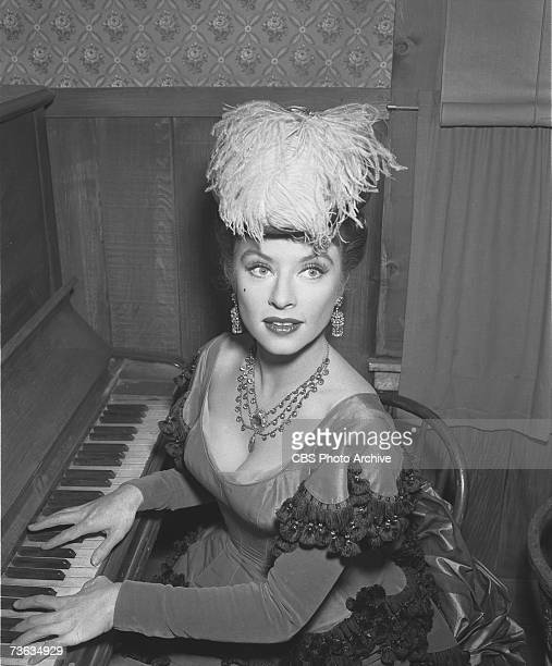 American television actress Amanda Blake sits at a piano in character as Miss Kitty Russell for the episode 'The Killer' of the CBS Western drama...
