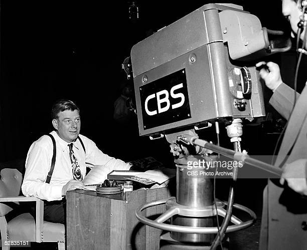 American television and radio host Arthur Godfrey sits at a desk and addresses a CBS television camera on the variety talent show 'Arthur Godrey's...