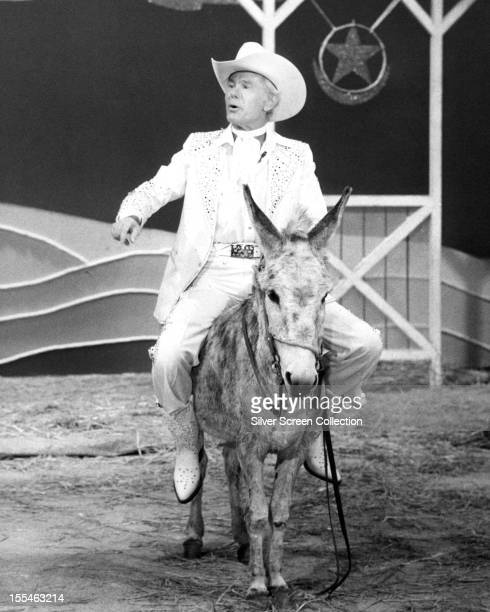 American television host and comedian Johnny Carson riding a stuffed donkey on his talk show 'The Tonight Show Starring Johnny Carson' circa 1985