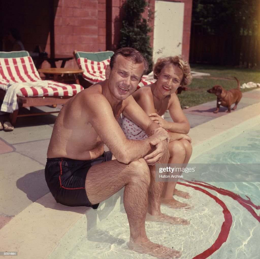 American television host Jack Paar (1918 - 2004) sits with wis wife Miriam beside their home swimming pool, early 1960s.