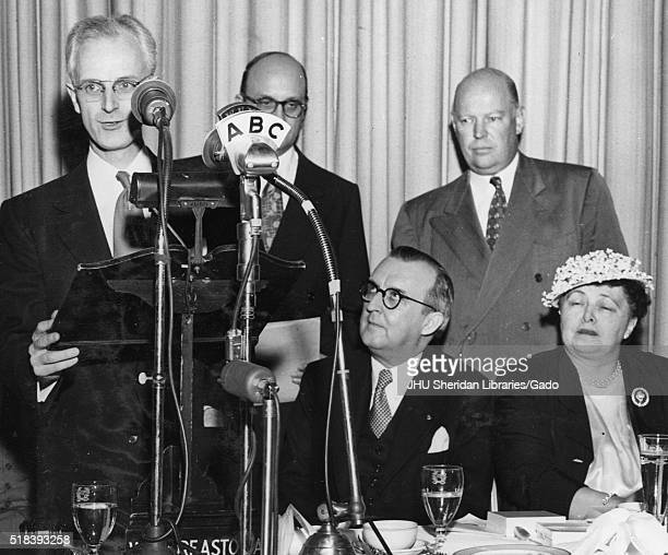 American television host Lynn Poole is standing at a special microphone with ABC printed on it, executives Ben Cohen and Dr Allen B DuMont are...