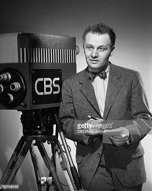 American television sports journalist and commentator Jim McKay stands next to a CBS television camera and holds a pencil and pad of paper in a...