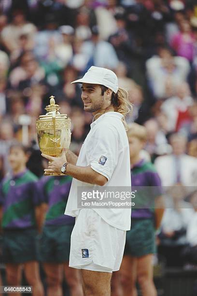 American tennis player Andre Agassi holds up the Gentlemen's Singles Trophy after defeating Goran Ivanisevic in the final of the Men's Singles...