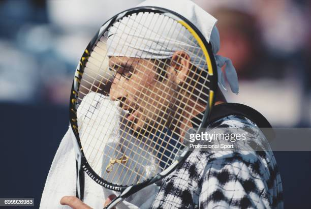 American tennis player Andre Agassi pictured wiping his face with a towel during a break in action during competition to progress to reach and lose...