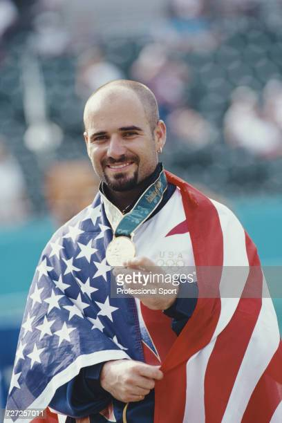 American tennis player Andre Agassi wrapped in the stars and stripes flag holds up his gold medal on the podium after winning the final of the Men's...