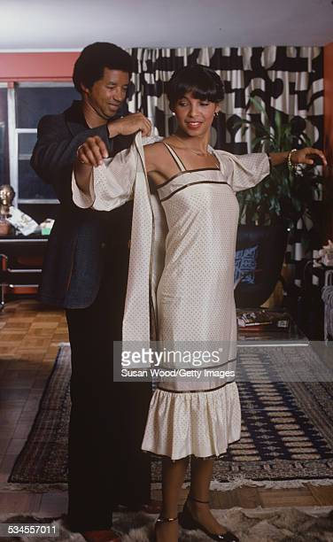 American tennis player Arthur Ashe helps his wife, photographer Jeanne Moutoussamy-Ashe, with her outfit, October 1977. The couple had married...