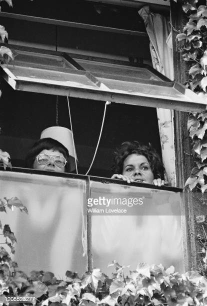American tennis player Billie Jean King and Australian tennis player Evonne Goolagong peering out of an awning window with their faces partially...