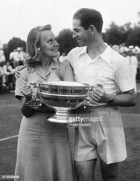 American tennis player Bobby Riggs and his wife hold the trophy he won by successfully defending his title in annual invitation tennis tournament at...