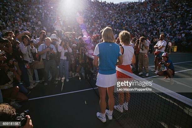 American tennis player Chris EvertLloyd and Martina Navratilova stand beside the net in front of press photographers before the final of the 1984 US...