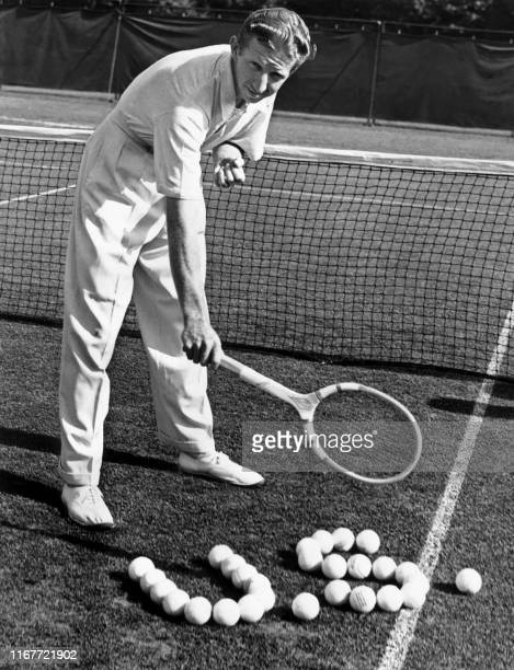 American tennis player Donald Budge sets up tennis balls to form a US during a practice at Merion Cricket Club here 30 august 1938 before his Davis...