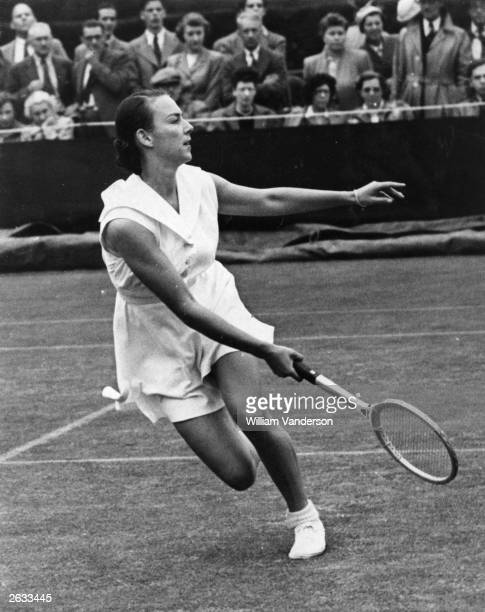 American tennis player Gertrude 'Gussie' Moran in action on the wet number three court at Wimbledon