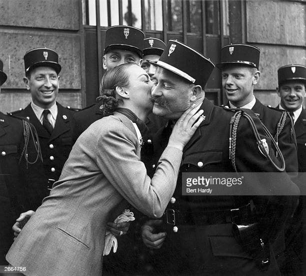American tennis player Gertrude Moran or Gorgeous Gussie kisses a member of the police parade at the Arc de Triomphe during a sightseeing tour of...