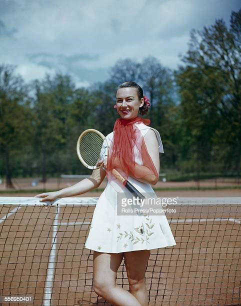 American tennis player Gussie Moran pictured posed on a tennis court with racket and red chiffon scarf tied around her neck circa 1950
