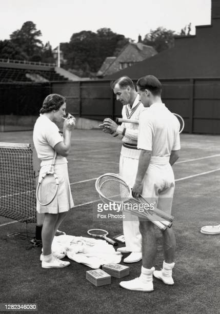 American tennis player Helen Jacobs lights a cigarette as compatriot Bill Tilden examines a tennis ball while Bunny Austin of Britain holding his...