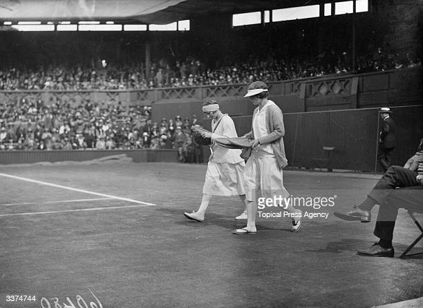 American tennis player Helen Wills and Britain's Kitty McKane walking out onto the court before their women's singles final match at the Wimbledon...