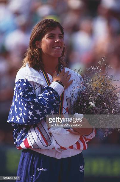 American tennis player Jennifer Capriati of the United States team celebrates on the medal podium after finishing in first place after beating Steffi...