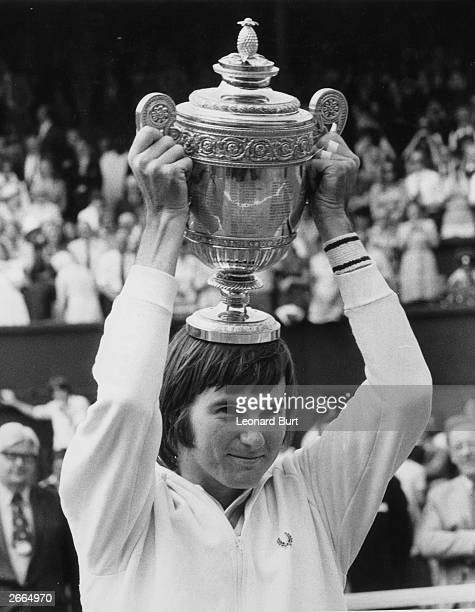 American tennis player Jimmy Connors holds aloft the men's singles trophy after beating Ken Rosewall in the final at the Wimbledon Tennis...