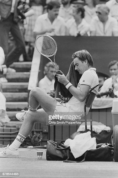 American tennis player Jimmy Connors pictured wiping his forehead with a towel during a break in play in his semifinal match against South African...