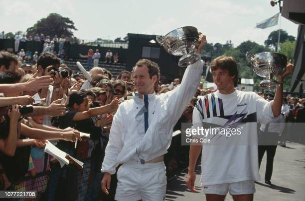 American tennis player John McEnroe and German tennis player Michael Stich lift their trophies after defeating Jim Grabb and Richey Reneberg both of...