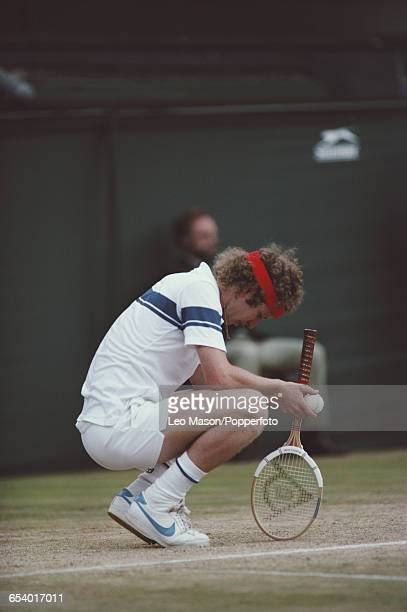 American tennis player John McEnroe crouching on the court during competition to reach the final and win the Men's Singles tournament by defeating...