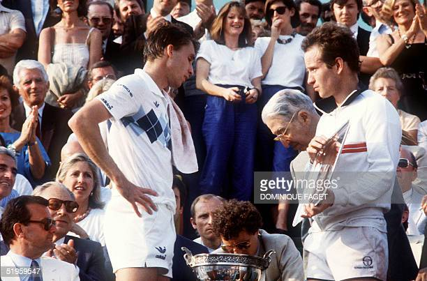 American tennis player John McEnroe holds the silver plate as Czekoslovakian player Ivan Lendl waits to receive the cup for his victory against...