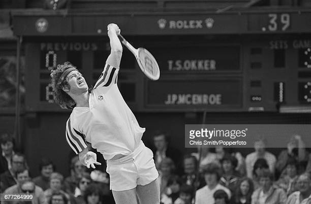 American tennis player John McEnroe pictured in action in his third round match against Dutch tennis player Tom Okker at the Wimbledon Lawn Tennis...
