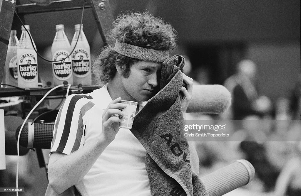American tennis player John McEnroe pictured wiping his forehead with a towel during a break in play as he competes to eventually lose the final of the Men's Singles tournament to Swedish tennis player Bjorn Borg, 1-6, 7-5, 6-3, 6-7, 8-6 at the Wimbledon Lawn Tennis Championships at the All England Lawn Tennis Club in Wimbledon, London on 5th July 1980.