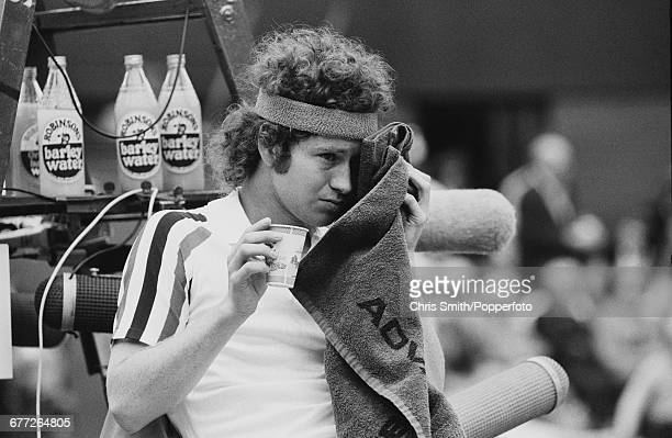 American tennis player John McEnroe pictured wiping his forehead with a towel during a break in play as he competes to eventually lose the final of...