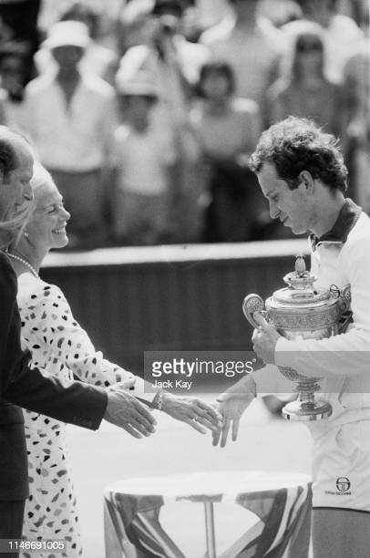 American tennis player John McEnroe presented with the trophy by the Duchess of Kent after his victory in the Men's Singles final during Wimbledon...