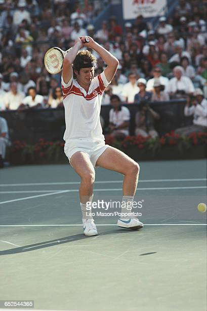 American tennis player John McEnroe raising his tennis racket over his head in anger during competition to progress to win the final of the 1980 US...