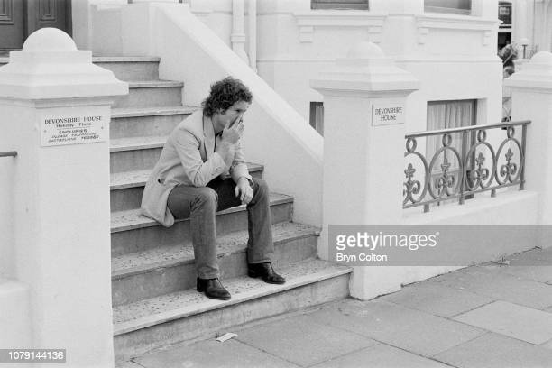 American tennis player John McEnroe sits on the steps of Devonshire House the rental flat of his girlfriend the American tennis player Stacy Margolin...
