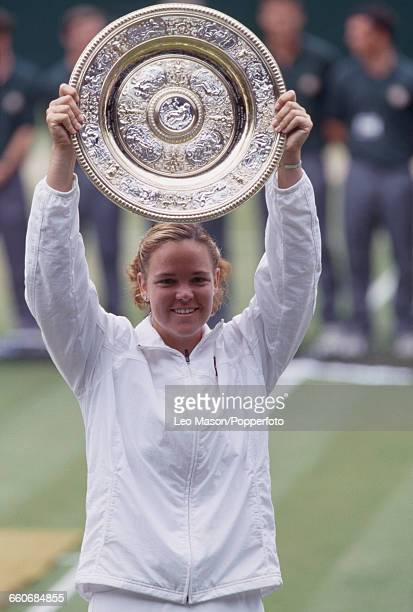 American tennis player Lindsay Davenport holds the Venus Rosewater Dish trophy up in the air after winning the final of the Women's Singles...