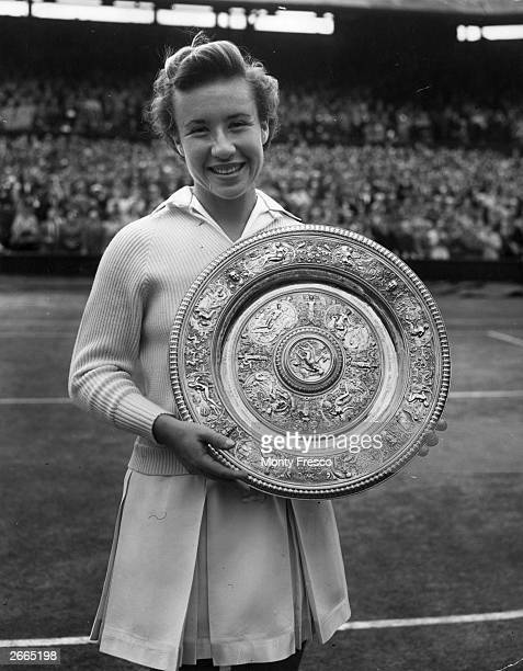 American tennis player Maureen Connolly holding the women's singles championship trophy after her victory at Wimbledon