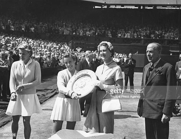 American tennis player Maureen Connolly receives the women's singles trophy from the Duchess of Kent on the centre court at Wimbledon after beating...