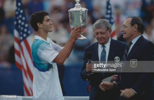 American tennis player Pete Sampras is handed the trophy after beating Andre Agassi 64 63 62 in the final of the Men's Singles tennis tournament to...