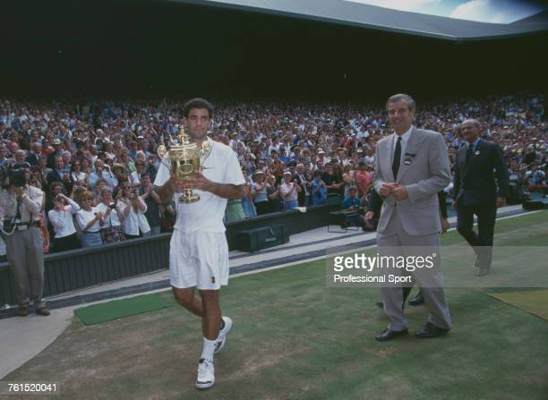 American tennis player Pete Sampras pictured holding the Gentlemen's Singles Trophy in front of cheering crowds after defeating French tennis player...