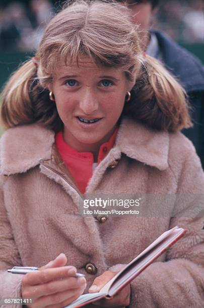 American tennis player Tracy Austin pictured signing an autograph book for a fan in England in 1977