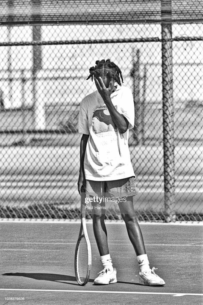 American tennis player Venus Williams, 11, covers her face after missing a serve during a training session at the Compton tennis courts, South Central Los Angeles, California, April 20 1991. Borth her and her sister, Serena, were being coached by their father, Richard Williams.