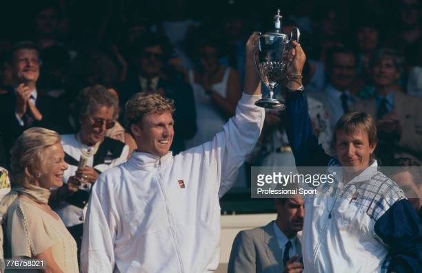 American tennis players Jonathan Stark and Martina Navratilova celebrate with the winners trophy after defeating Gigi Fernandez of United States and...