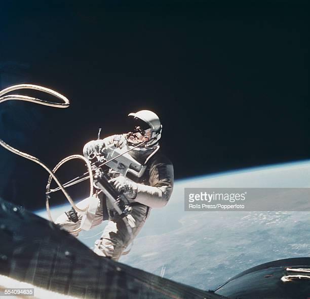 American test pilot and NASA astronaut Edward Higgins White becomes the first American to walk in space as he leaves the Gemini 4 space capsule above...